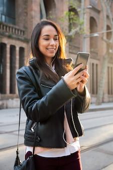 그녀의 전화에서 메시지를 읽고 웃는 젊은 여자