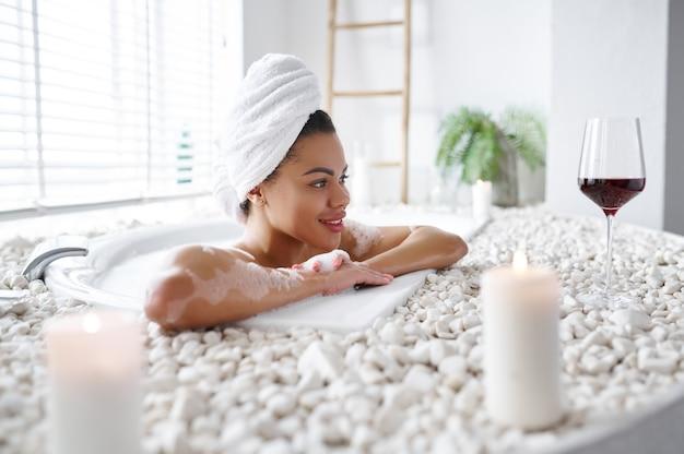 笑顔の若い女性は、泡風呂でリラックスします。バスタブの女性、スパの美容とヘルスケア、バスルームのウェルネストリートメント、背景の小石とキャンドル