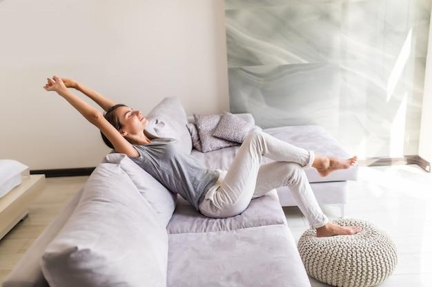 웃는 젊은 여자는 소파에 누워 휴식