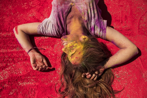 Smiling young woman relaxing on red holi color powder