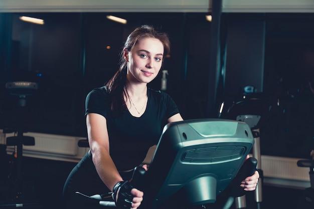 Улыбается молодая женщина, верхом на велотренажер в тренажерном зале