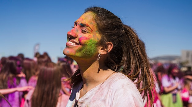 Smiling young woman's face painted with holi color