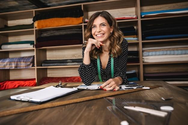 Улыбающаяся молодая женщина-швея работает в мастерской, выбирая текстиль