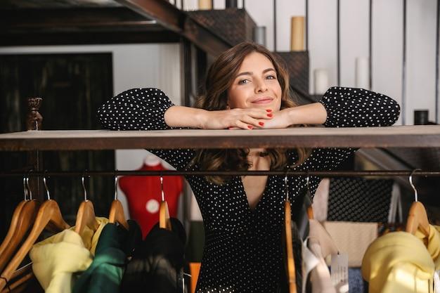 Улыбающаяся молодая женщина-швея работает в мастерской, стоя у вешалки для одежды