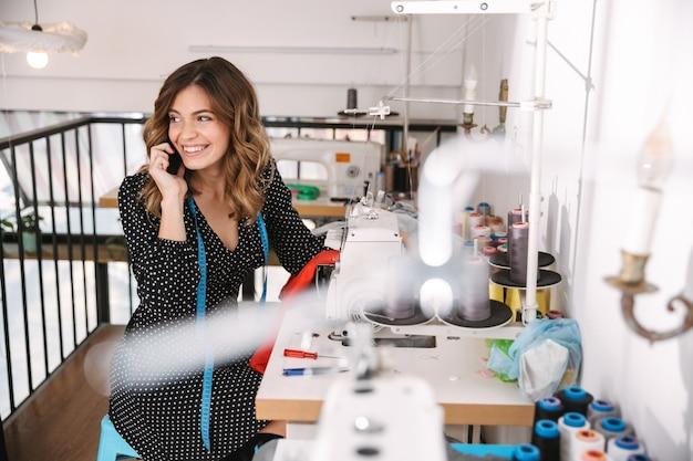 Улыбающаяся молодая женщина-швея работает в мастерской, используя швейную машину, разговаривает по мобильному телефону