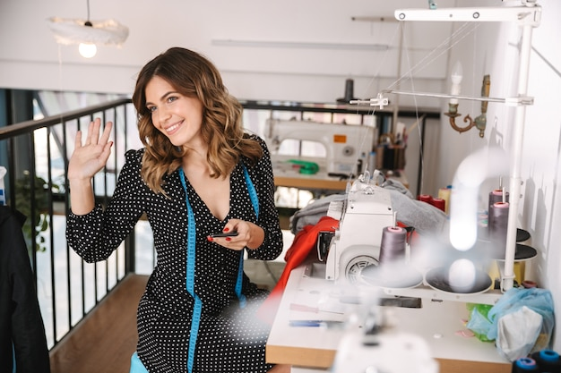 Улыбающаяся молодая женщина-швея работает в мастерской, используя швейную машину, машет рукой