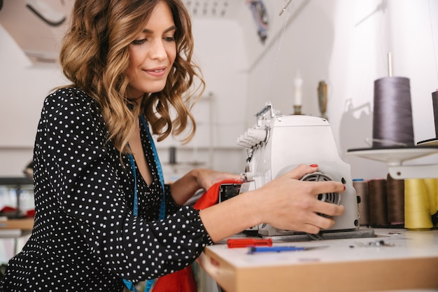 Улыбающаяся молодая женщина-швея работает в мастерской, используя швейную машину