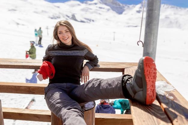 Улыбающаяся молодая женщина сидит и отдыхает после лыжной горы