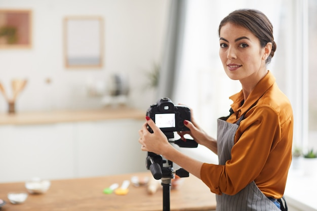 Smiling young woman setting up camera