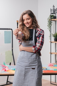 Smiling young woman showing black paintbrush