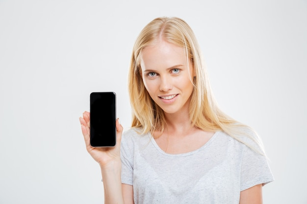 Smiling young woman showing blank smartphone screen isolated on a white wall