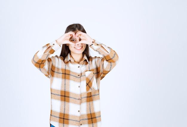 Улыбается молодая женщина, показывая жест сердца двумя руками.