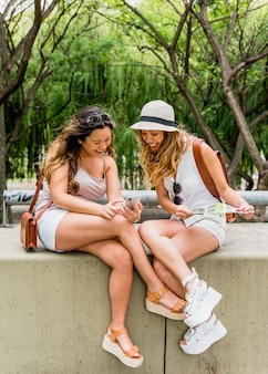 Smiling young woman showing her mobile phone to her female friend in the park