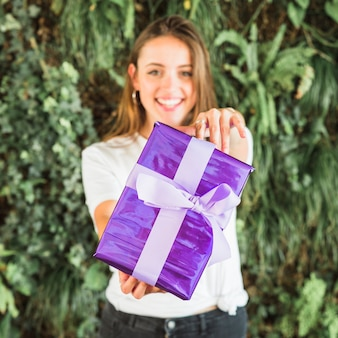 Smiling young woman showing purple gift box