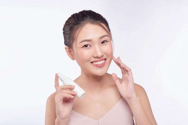 スキンケア製品を見せる笑顔の若い女性