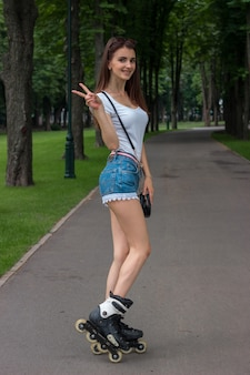 Smiling young woman shows hand gesture with two fingers and stands on rollers