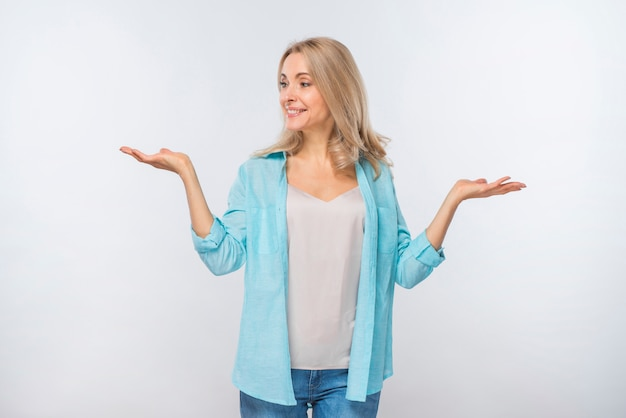 Smiling young woman shrugging isolated against white background