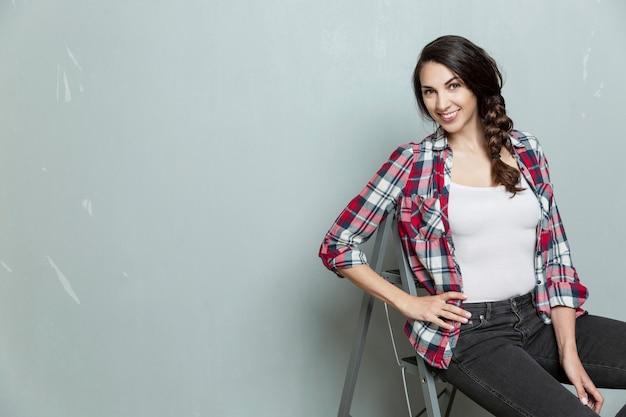 笑顔の若い女性は、灰色の壁を背景に脚立に座っています。ジーンズと格子縞のシャツの美しいブルネット。建設と修理。