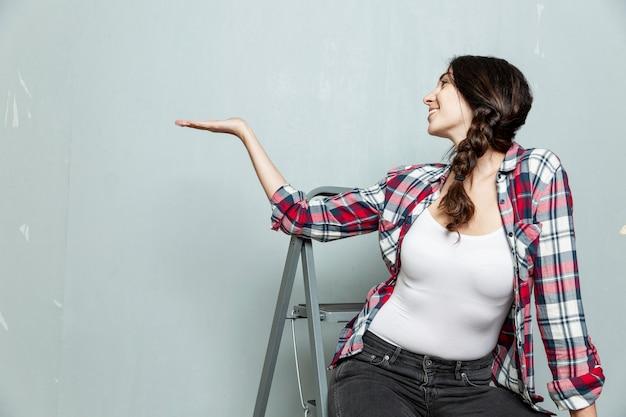 笑顔の若い女性が脚立に座って、灰色の塗られた壁を手で指しています。建設と修理。テキスト用のスペース。