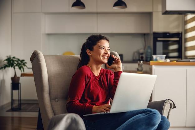 家に座って上司と電話で会話している若い女性の笑顔。膝の上で彼女はラップトップを持っています。コロナウイルスの概念中のリモートビジネス。