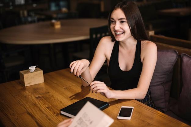 Улыбается молодая женщина, сидя в ресторане, держа перо в руке