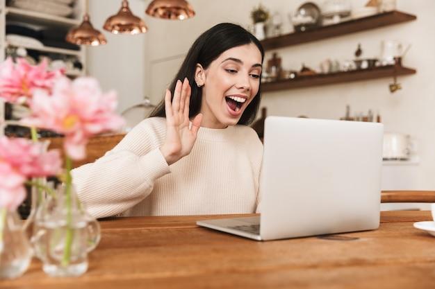 Улыбающаяся молодая женщина, сидящая на кухне и использующая портативный компьютер, имея видеозвонок