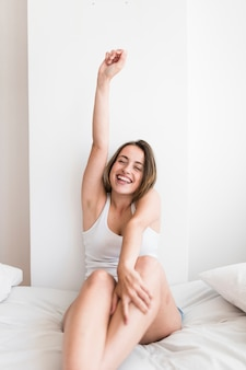 Smiling young woman sitting on bed stretching her arms