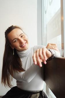 Smiling young woman sitting at cafe and looking at camera close-up