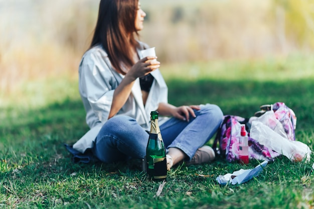 Smiling young woman sitting on grass and drinking wine