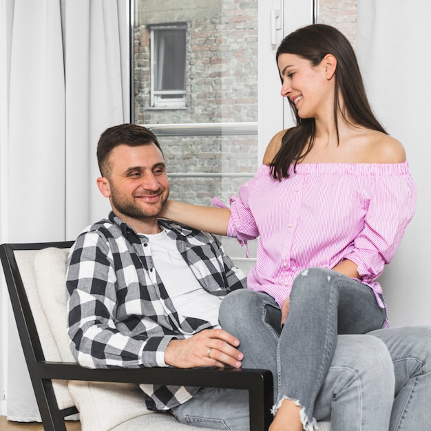 Smiling young woman sitting on her boyfriend's lap sitting on chair