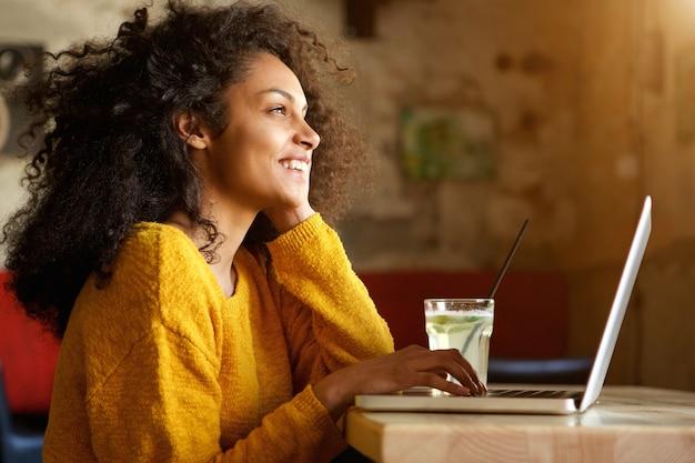 Улыбается молодая женщина, сидя в кафе с ноутбуком