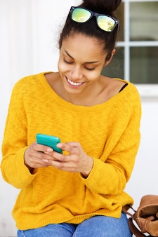 Smiling young woman sitting outside using mobile phone