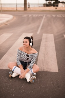 Smiling young woman sitting on road wearing roller skate listening music on headphone