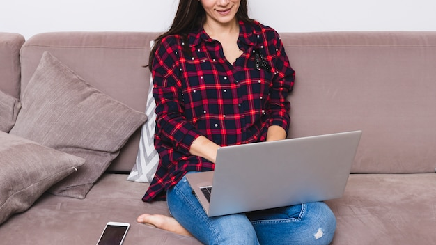 Smiling young woman sitting on sofa using laptop