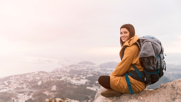 Smiling young woman sitting on the top of mountain with her backpack
