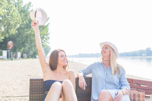 ビーチで帽子を持っている友達と一緒に座っている若い女性に