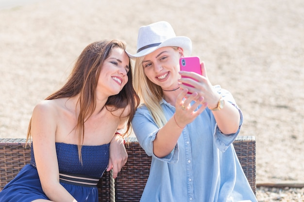 Smiling young woman sitting with her friend taking selfie with cellphone at beach