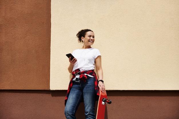 壁の近くで屋外でポーズをとっている間音楽を聴いて楽しんでスマートフォンを保持している木製の赤いスケートボードと笑顔の若い女性のスケートボーダー