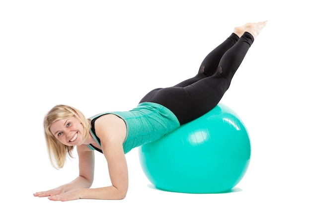 Smiling young woman in sportswear doing exercises with fitness ball. isolated over white background.
