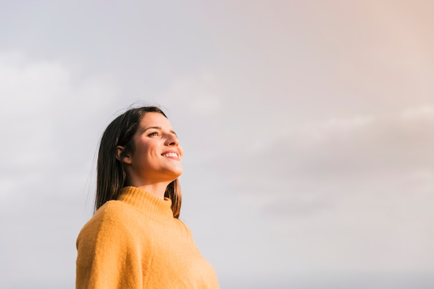 Smiling young woman standing against sky looking away