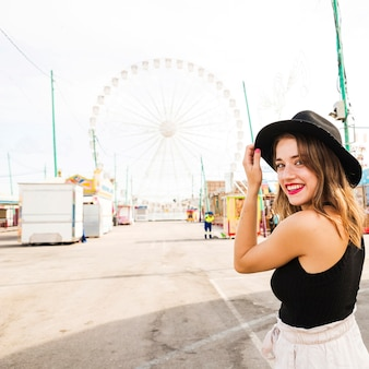 Smiling young woman standing at amusement park
