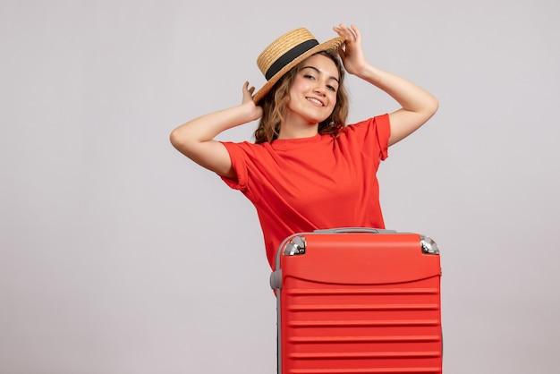 Улыбающаяся молодая женщина, стоящая за чемоданом на белом