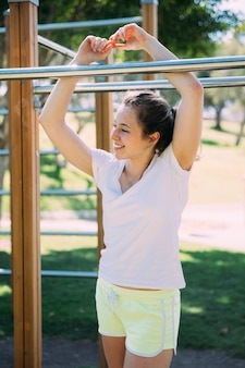 Smiling young woman standing by monkey bars