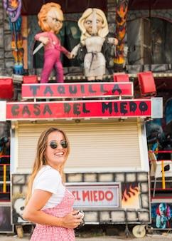 Giovane donna sorridente che sta davanti al giro divertito della casa infestata