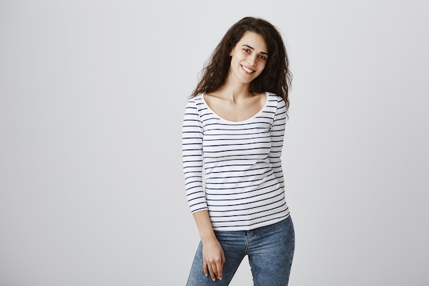 灰色の壁に立っている笑顔の若い女性