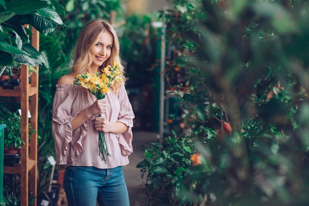 Улыбается молодая женщина, стоящая в питомнике растений, холдинг желтый букет цветов