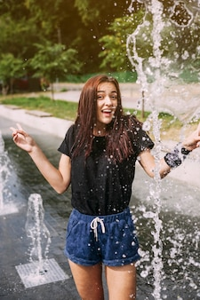 Smiling young woman standing near fountain making hand gesture