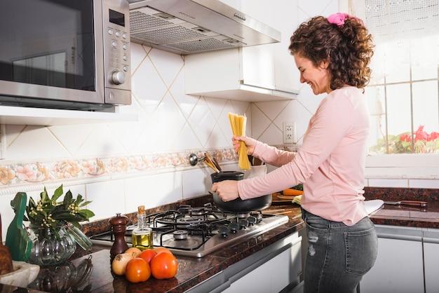 Улыбается молодая женщина, стоя возле газа, готовит спагетти на кухне