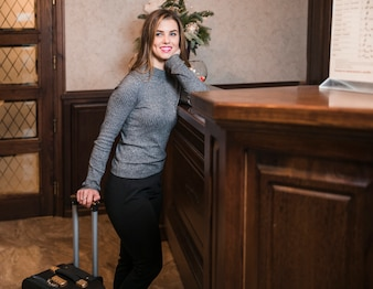 Smiling young woman standing near the reception desk in hotel