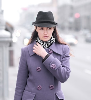 街の通りに立っている笑顔の若い女性。
